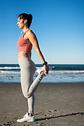Woman in her twenties stretching post-workout during an early morning on the beach in Newport, Rhode Island