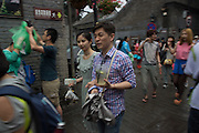People in the streets near Jingshan Park and the Forbidden City, on a rainly afternoon.