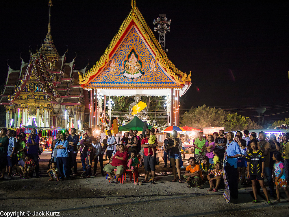 "14 MARCH 2014 - NAKHON CHAI SI, NAKHON PATHOM, THAILAND: People gather in the parking lot at Wat Bang Phra to watch an acrobatic troupe perform at the opening of the temple's tattoo festival. Wat Bang Phra is the best known ""Sak Yant"" tattoo temple in Thailand. It's located in Nakhon Pathom province, about 40 miles from Bangkok. The tattoos are given with hollow stainless steel needles and are thought to possess magical powers of protection. The tattoos, which are given by Buddhist monks, are popular with soldiers, policeman and gangsters, people who generally live in harm's way. The tattoo must be activated to remain powerful and the annual Wai Khru Ceremony (tattoo festival) at the temple draws thousands of devotees who come to the temple to activate or renew the tattoos. People go into trance like states and then assume the personality of their tattoo, so people with tiger tattoos assume the personality of a tiger, people with monkey tattoos take on the personality of a monkey and so on. In recent years the tattoo festival has become popular with tourists who make the trip to Nakorn Pathom province to see a side of ""exotic"" Thailand.   PHOTO BY JACK KURTZ"