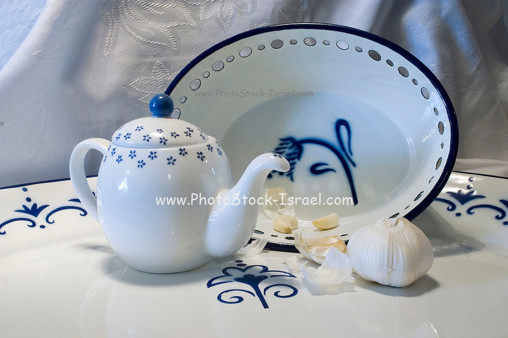Blue and white still life with a tea pot garlic and plates