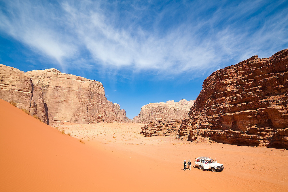 Tourists step out of a Jeep below red sand dunes in Wadi Rum, Jordan.