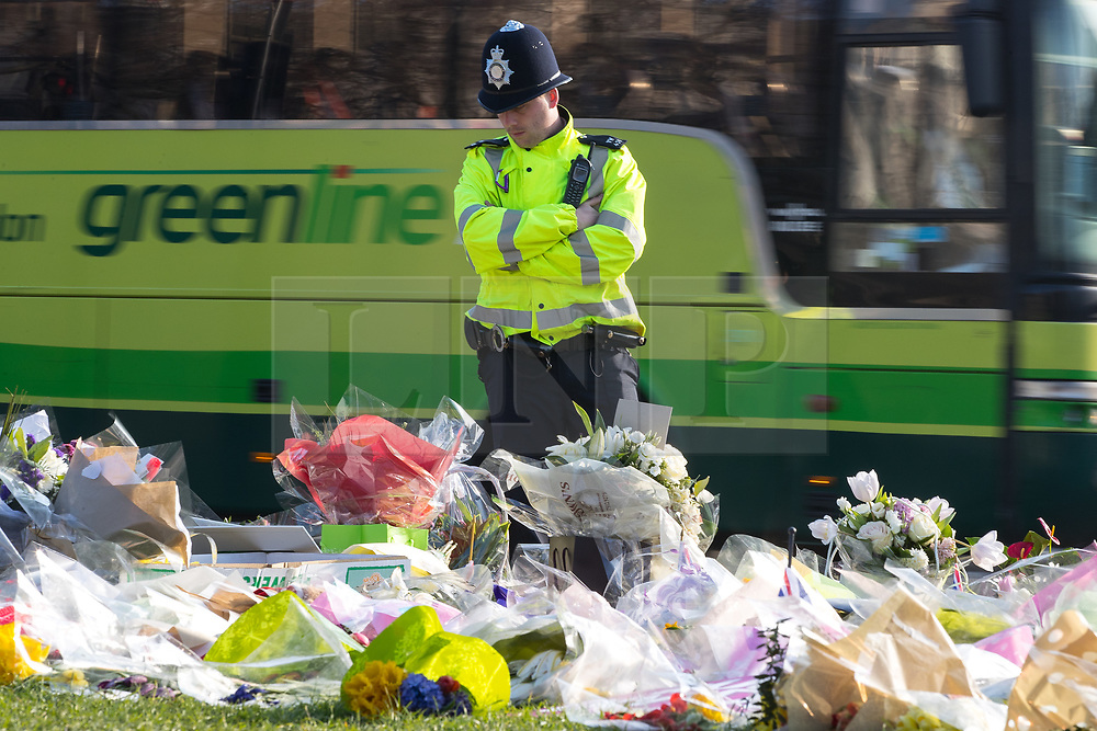 © Licensed to London News Pictures . 28/03/2017 . London , UK . A policeman looks at flowers and tributes in Parliament Square opposite Parliament in Westminster , in response to Khalid Masood's terrorist attack and the killing of PC Keith Palmer . Photo credit: Joel Goodman/LNP