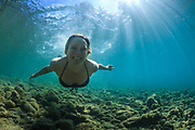A woman smiles as she swims in the clear blue waters of the Clutha River near Wanaka, New Zealand.