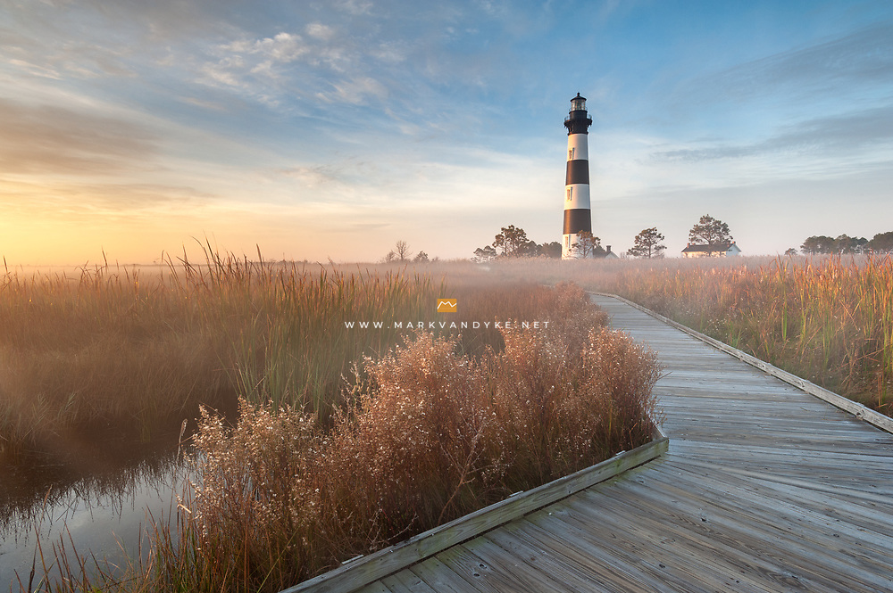 Radiant fog clings tightly to the autumn-tinted marsh grasses behind the Historic Bodie Island Lighthouse in the Outer Banks of North Carolina.  The lighthouse is part of Cape Hatteras National Seashore.
