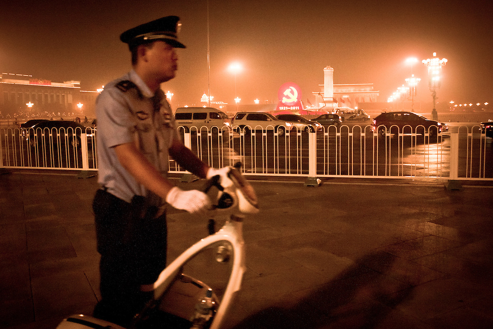 A chinese police officer is patrolling near Tiananamen square where a giant communist symbol has been installed for the CPC 90 years anniversary.