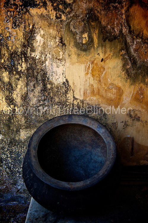 Cooking pot in a kitchen courtyard. A traditional square courtyard home called a Natcharam house. <br /> Jaffna homes. 2011