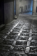Lamps and stone cobbles at night in cobbled street alleyway in Erice, Sicily, Italy