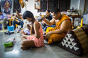 """22 MARCH 2013 - NAKHON CHAI SI, NAKHON PATHOM, THAILAND: A monk blesses a woman's new Sak Yant tattoo at Wat Bang Phra during the tattoo festival. Wat Bang Phra is the best known """"Sak Yant"""" tattoo temple in Thailand. It's located in Nakhon Pathom province, about 40 miles from Bangkok. The tattoos are given with hollow stainless steel needles and are thought to possess magical powers of protection. The tattoos, which are given by Buddhist monks, are popular with soldiers, policeman and gangsters, people who generally live in harm's way. The tattoo must be activated to remain powerful and the annual Wai Khru Ceremony (tattoo festival) at the temple draws thousands of devotees who come to the temple to activate or renew the tattoos. People go into trance like states and then assume the personality of their tattoo, so people with tiger tattoos assume the personality of a tiger, people with monkey tattoos take on the personality of a monkey and so on. In recent years the tattoo festival has become popular with tourists who make the trip to Nakorn Pathom province to see a side of """"exotic"""" Thailand. The 2013 tattoo festival was on March 23.    PHOTO BY JACK KURTZ"""