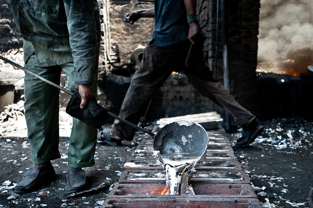 A man works in an aluminum smelting workshop, pouring melted aluminum into trays where it will cool into ingots.