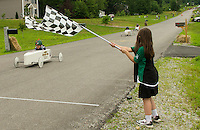 Leia Donahue waves the checkered flag as Brady Palmer crosses the finish line in first place during the final heat with Justin Vayda, Michael Moses and Jeremy Sandock at the 2nd annual Franklin Elks Soap Box Derby on Saturday.  (Karen Bobotas/for the Laconia Daily Sun)