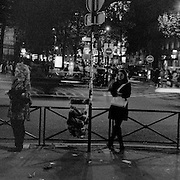Individuals wait on a street corner in the Odeon district during a dark winters evening in Paris, France. October 22, 2007. Photo Tim Clayton..Paris is often known as 'The City of Love' but like any major City in the world, the inhabitants often live a singular existence, going about their daily lives in relative solitude. Parisians are respectful of each others space, often courteous and polite while extremely conscious of their own image. While love can be seen openly around the streets of Paris, so can the separate lives of Parisians.