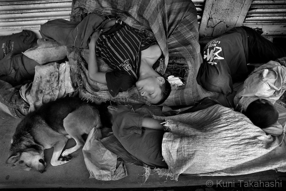 Street children sleep on sidewalk in Kathmandu, Nepal, on May 2010.<br /> Photo by Kuni Takahashi