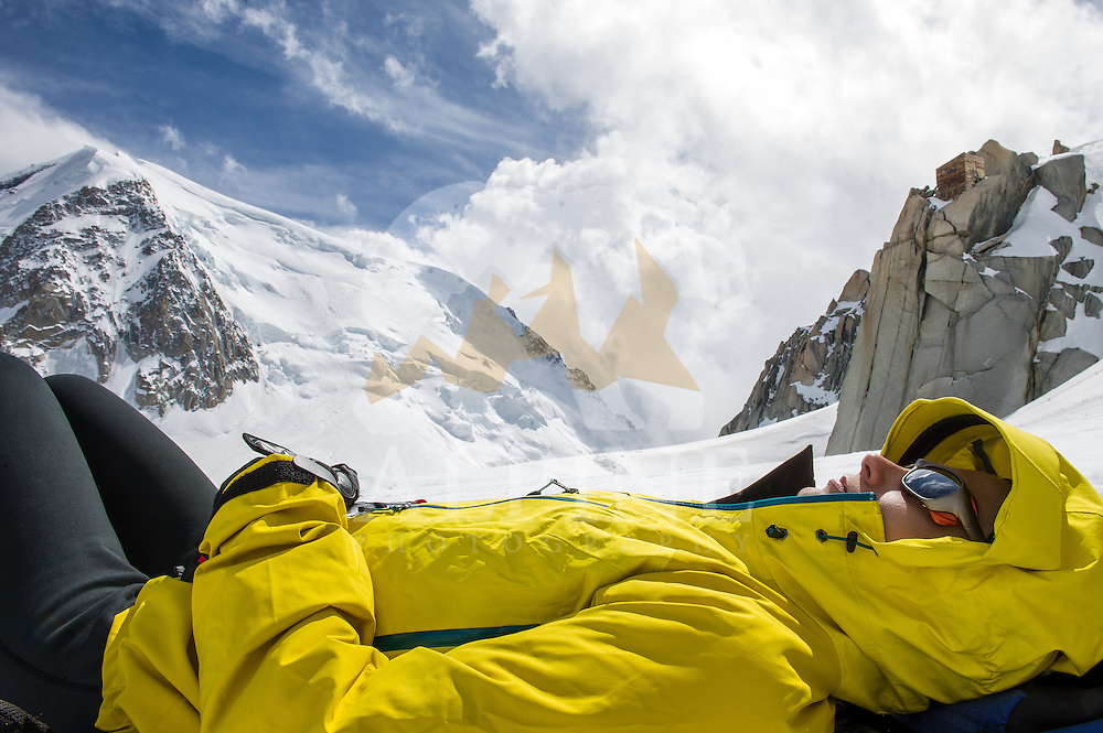 A female climber as seen resting on a sunny day on Col du Midi, at the foothills of Aiguillle du Midi, Chamonix, France, with the Norh Face of Mont Blanc du Tacul in the background.