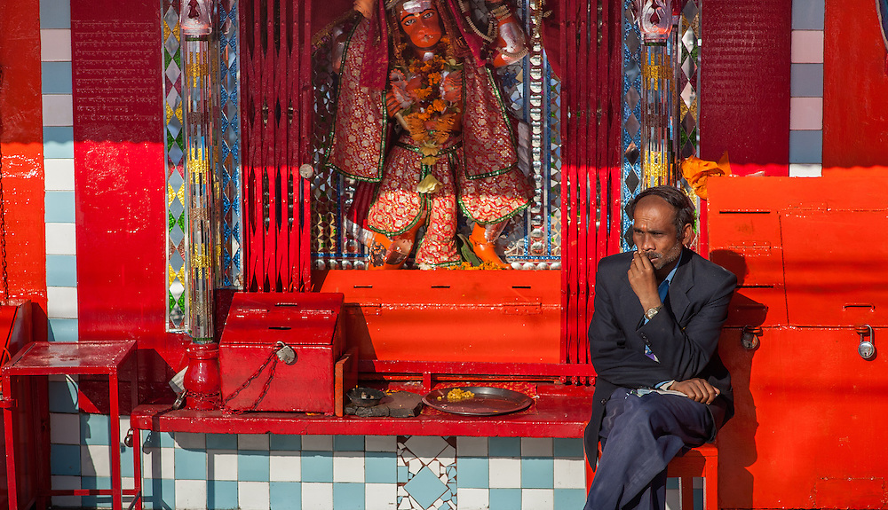 Man sitting at red Hanuman shrine (India)