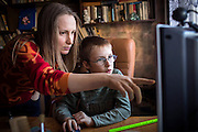Yaroslav, 10, is using the computer next to his mother Olga, 36, inside the provisional home where they reside as internally displaced persons. (IDPs) Yeroslav is taking part to the UNICEF-sponsored One Minute Junior project for internally displaced persons (IDPs), carried out by the local NGO 'Ukrainian Frontiers' in the city of Kharkiv, the country's second-largest, in the east. The conflict between Ukrainian army and Russia-backed separatists nearby, in the Donbass region, have left more than 10000 dead since April 2014, including over 1000 since the shaky Minsk II ceasefire came into effect in February 2015. The approximate number of people displaced by the conflict is 1.4 million as of August 2015. Yeroslav's mother, Olga, is also a participant to a different project of 'Ukrainian Frontiers', called 'Self-Employment', first as a beneficiary, and now as a paid hotline coordinator for people seeking jobs and formation courses.