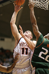 Laurynas Mikalauskas (11) shoots over Miami's Robert Hite (22).  Mikalauska had 12 points on the game to help the Hoos to a 71-51 victory.