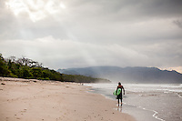 A surfer walks down the beach, Santa Teresa, Costa Rica