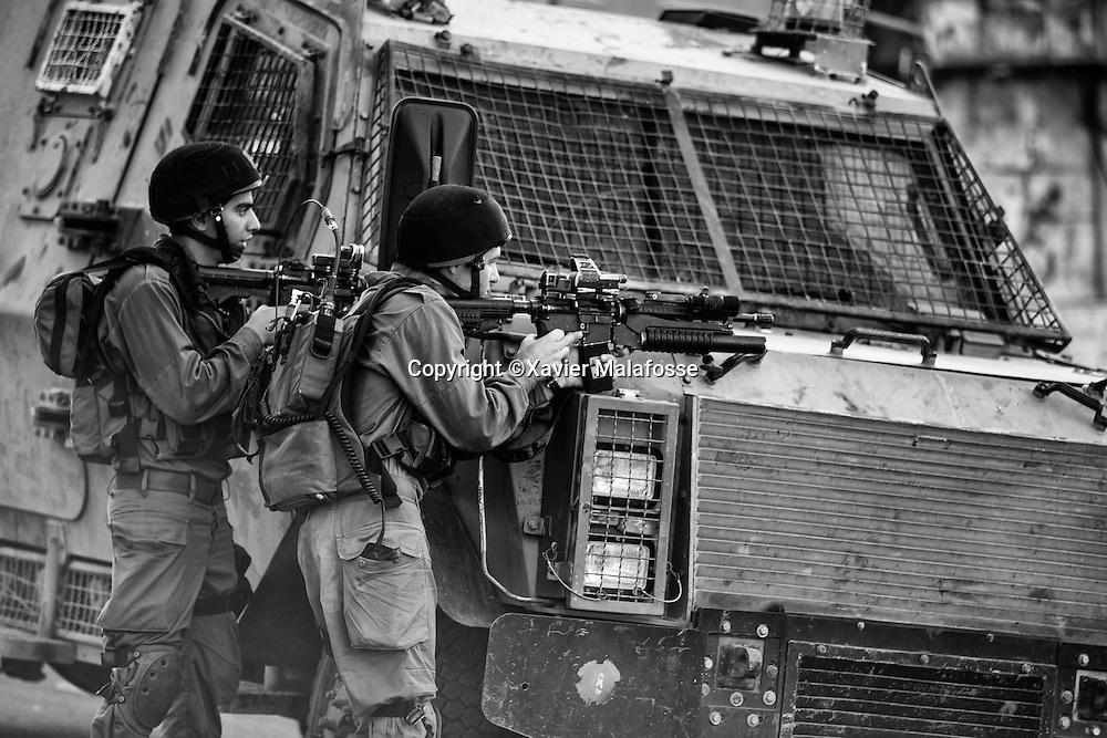 Devant le checkpoint de Bal al Zawiya, des soldats tiennent en respect les Palestiniens tentés de s'approcher.