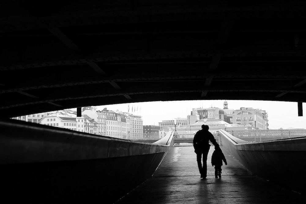 A mother with her kid pass under the Pont du Mont-Blanc.