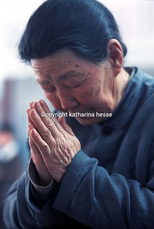 LIUJIAZHUANG VILLAGE, 8 APRIL 2001: a 78 year old women prays on Palm Sunday in an official church.China cut relations with the Vatican in the early fifites and since then, established a Patriotic catholic Church that's controlled by Chinese authorities.<br />Catholics who refused to give up their ties with the Vatican, started worshipping in underground churches and consequently were persecuted for a long time. Since the late nineties though, relations with the Vatican informally started to improve. Although China still has no diplomatic relations, many representatives from official churches met the pope John Paull II secretely . The Vatican, under the pope's leadership, has made several efforts to recover the tie with China. In February 2006 , Hong Kong Bishop Joseph Zen was named one of the first 15 new cardinals, which is seen by many as a gesture of goodwill and a significant step towards recovering the Vatican-China relationship.