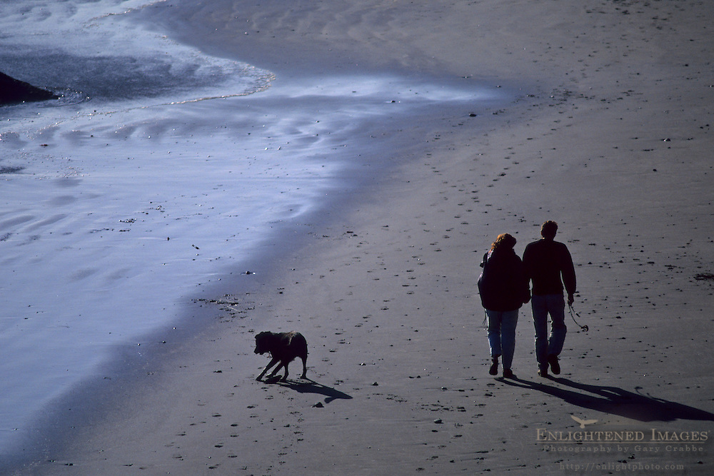 Couple and pet dog walking on Enderts Beach, Crescent City, Del Norte County, California