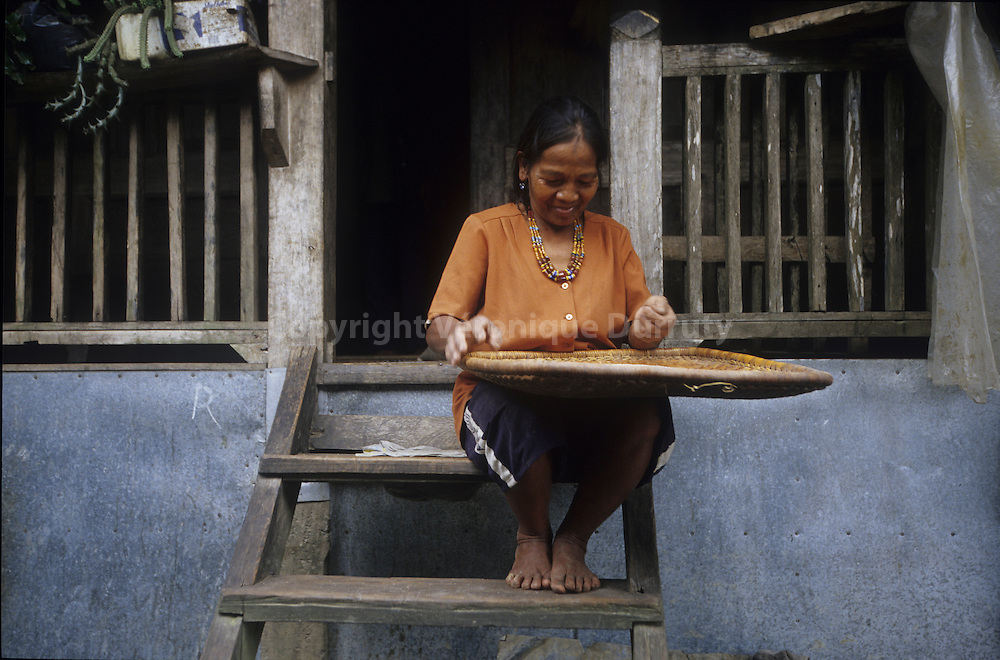 KALINGA - HEAD HUNTERS TRIBE-OLD WOMAN PREPARING THE RICE, LUZON ISLAND, THE PHILIPPINES