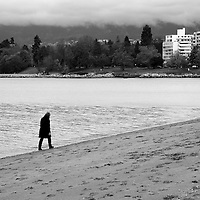 A lone person walking along a deserted beach, head down, with trees and city in background.