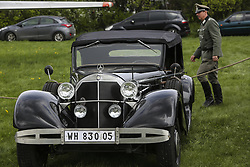 April 27, 2018 - Kiev, Ukraine - Re-enactor wearing Nazi uniform walks past an WWII era Mercedes-Benz 770 during an Old Car Land show at Aviation Museum in Kyiv, Ukraine, April 27,   2018  (Credit Image: © Sergii Kharchenko/NurPhoto via ZUMA Press)