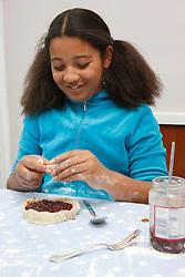 Portrait of mixed race girl making jam tarts