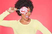 Portrait of an African American woman holding candy over her eye against colored background