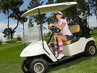 Young female golfer in sitting in cart smiling