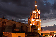 03 APRIL 2004 - SAN MIGUEL DE ALLENDE, GUANAJUATO, MEXICO: The bell tower of Iglesia San Rafael, foreground, and the top of of the spire of the Parroguia, the main Catholic church in San Miguel de Allende, Mexico. San Miguel, which was founded in the 1600s, is one of Mexico's premier colonial cities. It has very strict zoning and building codes meant to preserve the historic nature of the city center. About 7,500 US citizens, mostly retirees, live in San Miguel. PHOTO BY JACK KURTZ