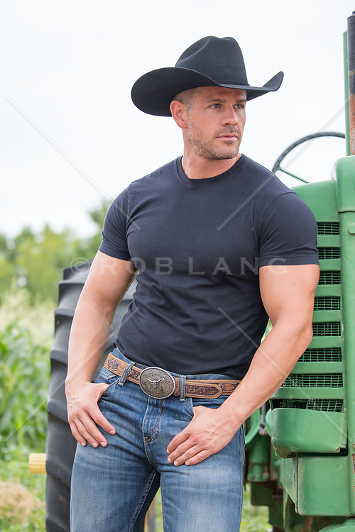 hot muscular cowboy leaning on a tractor