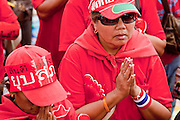 "Mar. 27, 2010 - BANGKOK, THAILAND:  Thai women bow their heads in the ""Wai"" or traditional Thai greeting when Red Shirt leader Veera Musigapong took the stage to speak Saturday, March 27. More than 80,000 members of the United Front of Democracy Against Dictatorship (UDD), also known as the ""Red Shirts"" and their supporters marched through central Bangkok March 27 during a series of protests against and demand the resignation of current Thai Prime Minister Abhisit Vejjajiva and his government. The protest is a continuation of protests the Red Shirts have been holding across Thailand. They support former Prime Minister Thaksin Shinawatra, who was deposed in a coup in 2006 and went into exile rather than go to prison after being convicted on corruption charges. Thaksin is still enormously popular in rural Thailand.    PHOTO BY JACK KURTZ"
