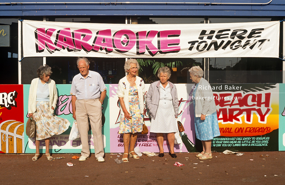 Pensioners on holiday - or on a daytrip - at the Nofilk seaside town of Great Yarmouth wait for a friend beneath a wide banner advertising a Karaoke event at the venue behind them that night. There are four old ladies and one man in the group, all dressed in summer clothes for their day at the beach. Only the gentleman is looking our way as the women are otherwise occupied. There is litter at their feet and garish posters are behind them. The man is outnumbered, a gender ratio of 4 to 1.