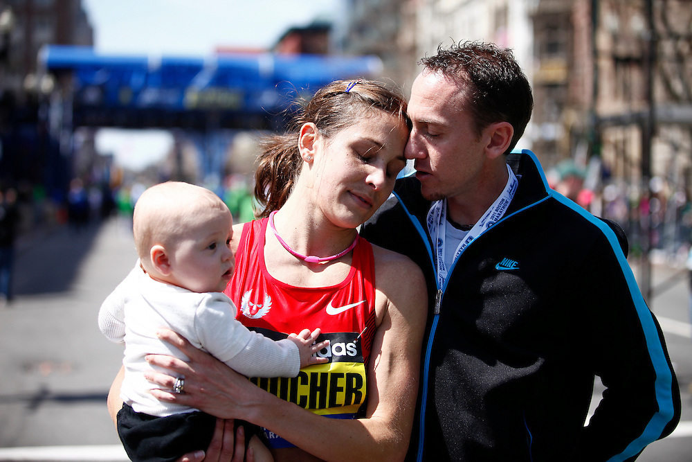Fifth place finisher, Kara Goucher is greeted by her husband and six-month-old son after running the 115th Boston Maratrhon, April 18, 2011.