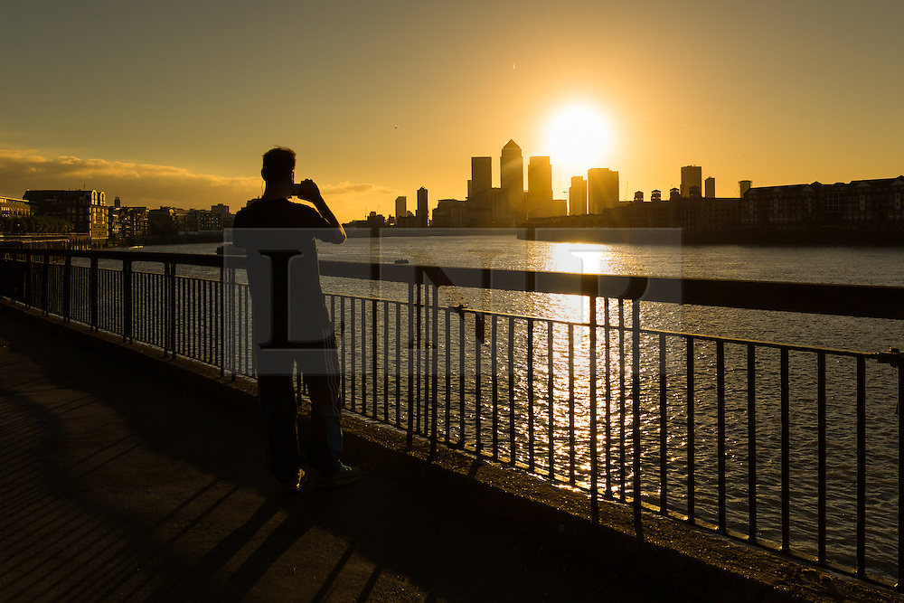 © Licensed to London News Pictures. 05/10/2016. LONDON, UK.  A man takes a photograph on the River Thames path as the sun rises behind Canary Wharf and London's financial district this morning. Forecasters are predicting a day of clear and sunny weather in London today.  Photo credit: Vickie Flores/LNP