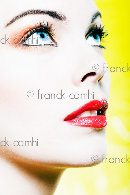 beautiful caucasian woman portrait with colorful make-up studio on yellow background