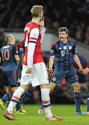 Arsenal's Per Mertesacker walks past Bayern Munich's Thomas Muller celebrations - Photo mandatory by-line: Joe Meredith/JMP - Tel: Mobile: 07966 386802 19/02/2014 - SPORT - FOOTBALL - London - Emirates Stadium - Arsenal v Bayern Munich - Champions League - Last 16 - First Leg