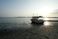An early morning low tide grounds a fishing boat near Cedar Key, Florida.