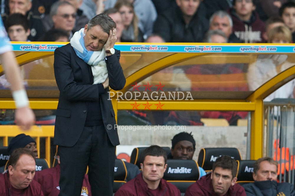 WOLVERHAMPTON, ENGLAND - Saturday, October 30, 2010: Manchester City's manager Roberto Mancini looks dejected as his side lose 2-1 to Wolverhampton Wanderers as substituted striker Emmanuel Adebayor sits on the bench during the Premiership match at Molineux. (Pic by: David Rawcliffe/Propaganda)