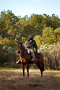 Bill Greene runs the scent as the fox during the Middleton Place foxhunt at Middleton Place plantation in Charleston, South Carolina. The hunt is a drag hunt where a scented cloth is used instead of live fox.<br /> (Photo by Charleston SC Photographer Richard Ellis Photography)