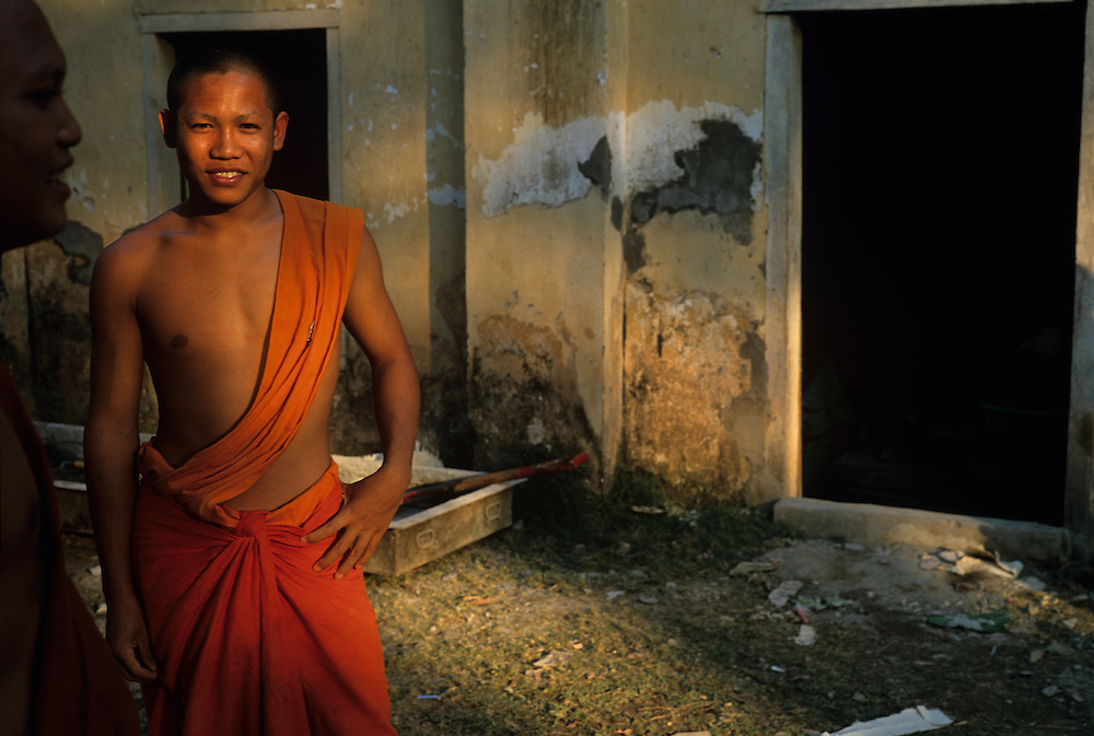 Asia, Laos, Luang Prabang,  Portrait of young Buddhist monk at Wat Nong Sikhunmeuang Temple at sunset