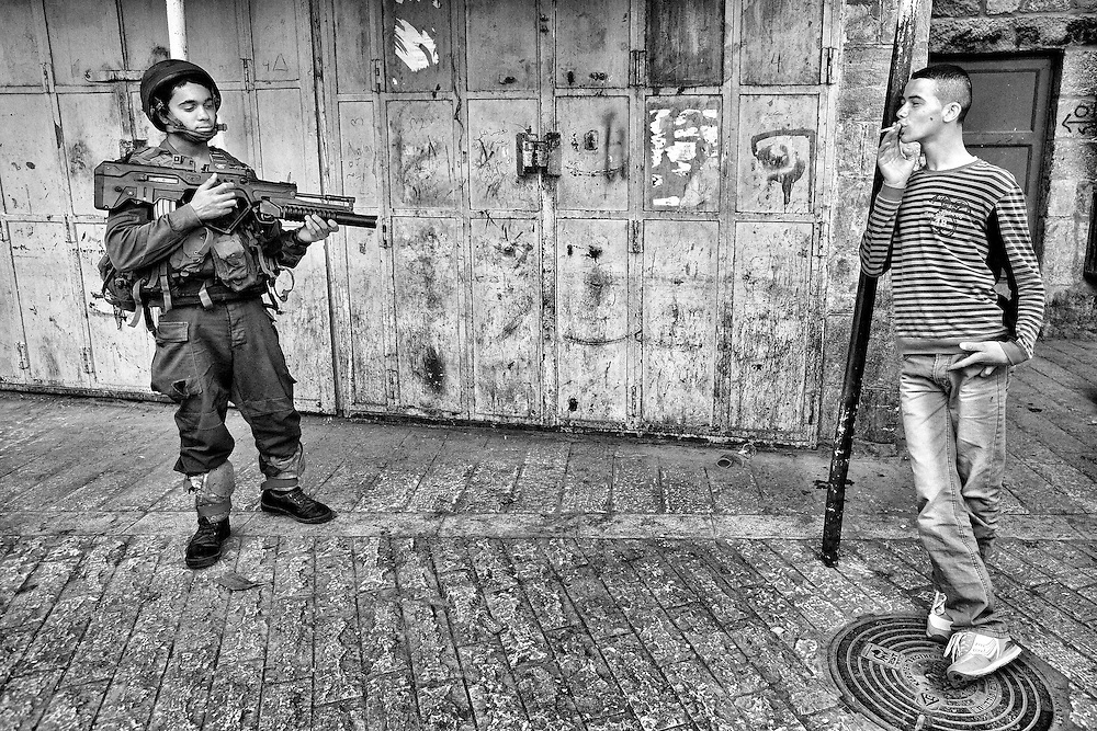A Palestinian boy taunts a young, yet heavily armed Israeli soldier in Hebron. Mar. 19, 2011. West Bank, Palestine.