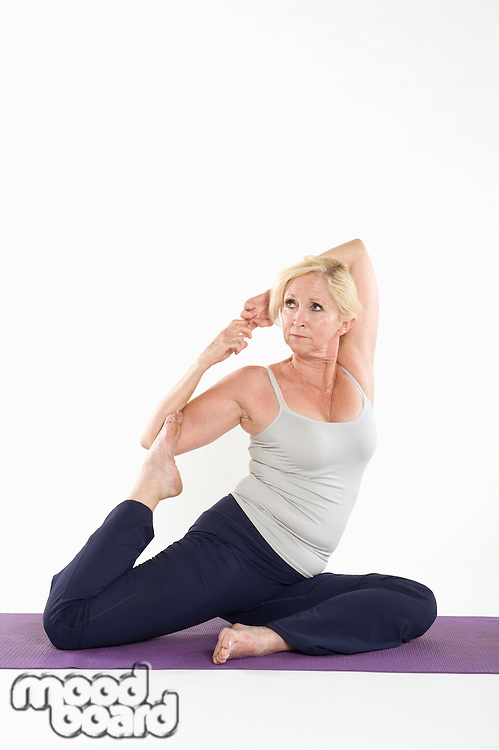 Middle aged woman stretching on yoga mat over white background