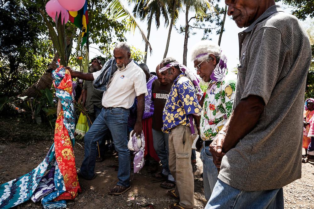 A l'entrée de la tribu, une première coutume est célébrée par les oncles maternels de l'époux. Ils demandent l'accès à la tribu pour débuter les cérémonies. L'orateur brandit la coutume bras tendu. Elle est composée d'une igname chef coiffée de feuilles de cordyline, d'argent et de tabac, le tout enroule dans trois manu qui s'étendent au sol. – Mariage Kanak  - Tribu de Méhoué, Canala – Nouvelle Calédonie – Septembre 2013