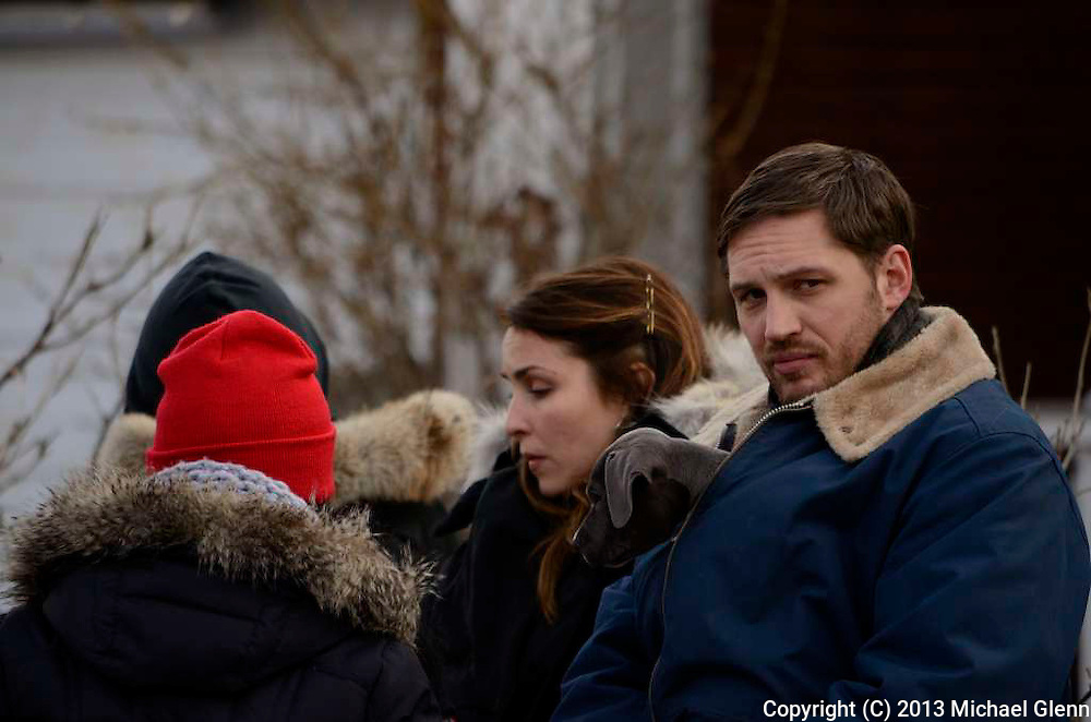 Tom Hardy standing with Noomi Repace looks at the camera while keeping his furry little co-star warm on the set of Animal Rescue