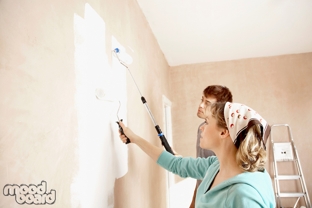 Couple painting wall with paint rollers indoors