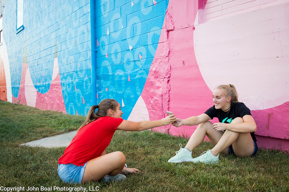 North Hagerstown High School classmates, Cira Bickford, 16, left, shows a picture of her friend, Olivia King, 17, in front of a massive mural painted on the side of a former grain mill in downtown Hagerstown, Maryland, on Tuesday, September 26, 2017. Originally a District that was mostly rural, but included towns like Frederick and Hagerstown, Maryland's 6th District was redistricted in 2011, combining rural northern Maryland regions with more affluent communities like near Washington D.C. turning the district from Republican to Democrat. <br />  <br /> CREDIT: John Boal for The Wall Street Journal<br /> GERRYMANDER