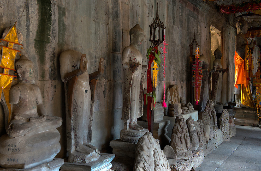 A parade of ancient statues lines the corridor of Angkor Wat's central shrine.